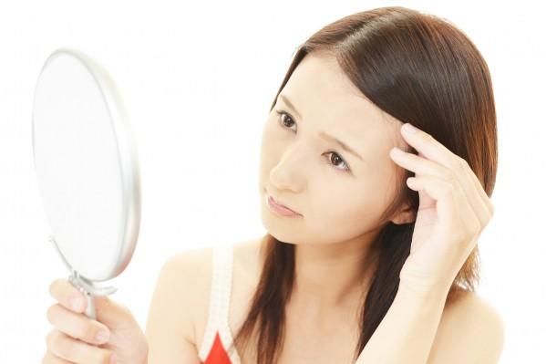 髪の毛を鏡で見る女性